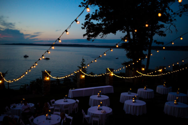 Sunset of Puget Sound with reception tables on lawn with string light overhead, summer wedding