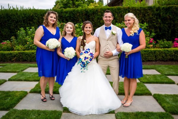 Bride in White with Bridesmaids in blue with blue and white bouquets.  Summer Wedding