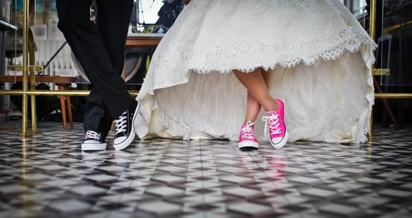 Bride and groom with converse on their feet in their wedding attire at wedding shows