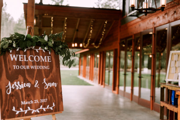 Rustic welcome sign at wedding with a eucalyptus topper