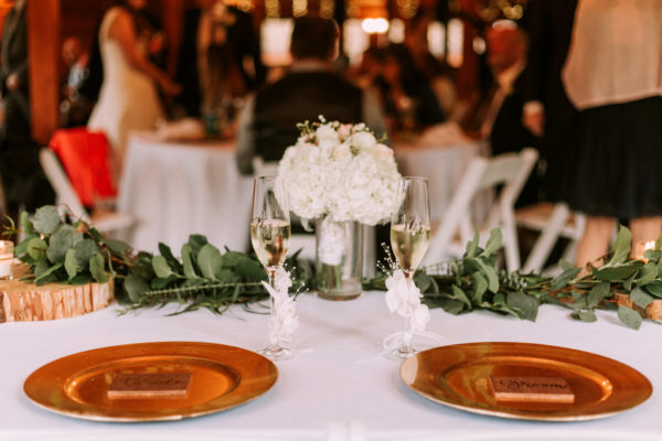 Gold chargers on white cloth with elegant white hydrangeas in a vase surrounded by eucalyptus, It's all in the Details