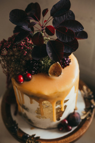 Organic cake with dripping icing with fresh flowers and fruit