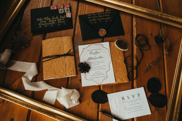 black and gold hand lettered invitation suite laying on a rustic wood table, It's all in the Details