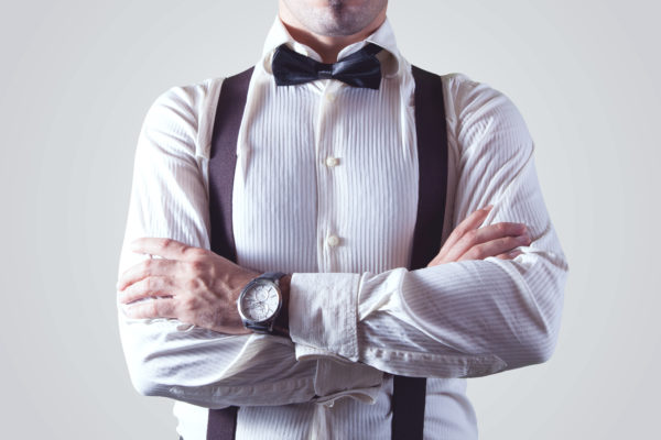 Groom in white shirt, black bow tie and suspenders